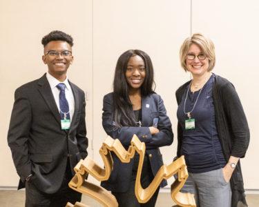 Two students (Jarrett Thomas and Jai Huntley) stand with their professor (Laura Battaglia) at ORNL