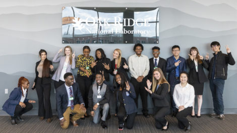 The student presenters from the 2020 Final Competition pose in front of an Oak Ridge National Laboratory sign.